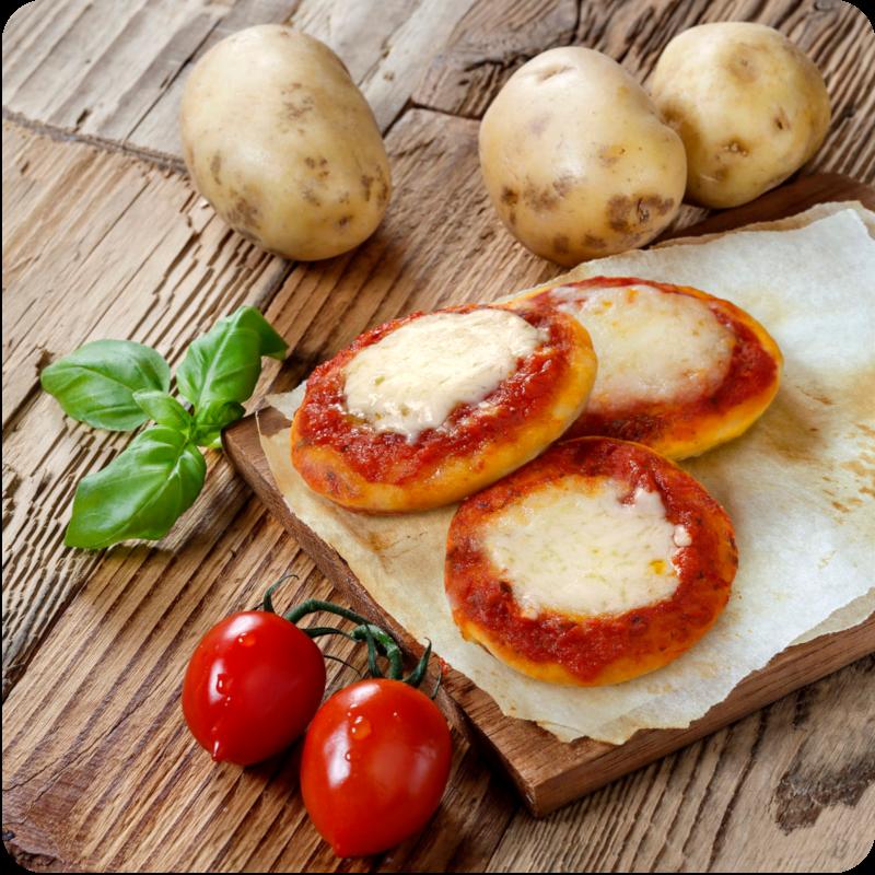 pizzette al gusto margherita disposte su tagliere con patate, pomodorini e basilico disposti intorno